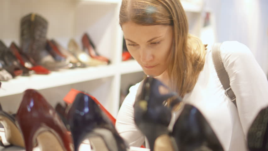 View through store glass window. Young woman shopping for shoes in mall. Choosing black stilettos. Rows of shoes foreground and on background