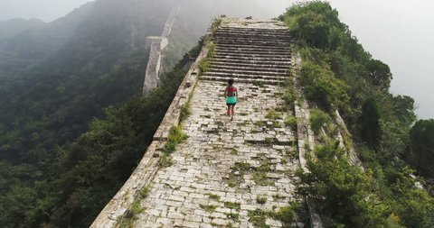 aerial flying drone view of  young fitness woman trail runner running on great wall