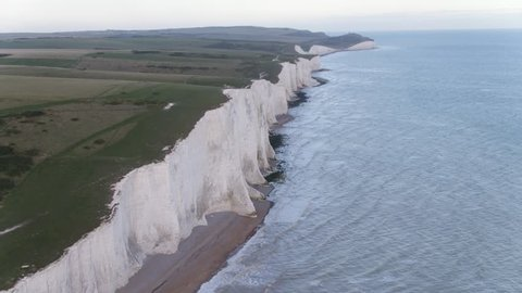 Slow aerial flight with anti-clockwise gentle pan of white chalk cliffs from Seven Sisters to Beachy Head finishing over cliff plateau in the UK