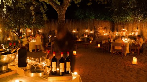 Sabi Sands, Mpumalanga, South Africa - 03/30/2017 A joyful evening as the lodge guests enjoy a boma dinner around the campfire under a majestic Marula tree at Londolozi.