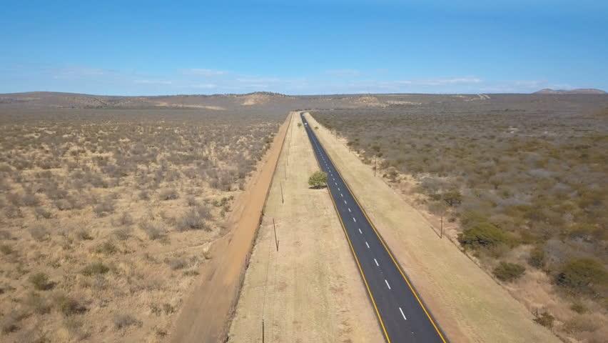 Asphalt road with wide fire break in arid bush veld aerial shot | Shutterstock HD Video #31327756