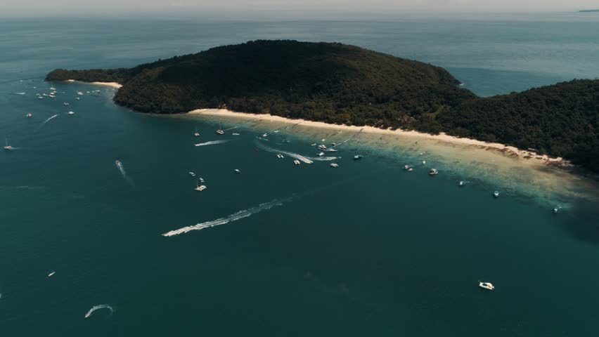 The flight and shooting of the beautiful island of Thailand after a tropical rainstorm and in sunny weather. A beautiful beach strip, numerous yachts moored to the pier, tropical jungle landscape and