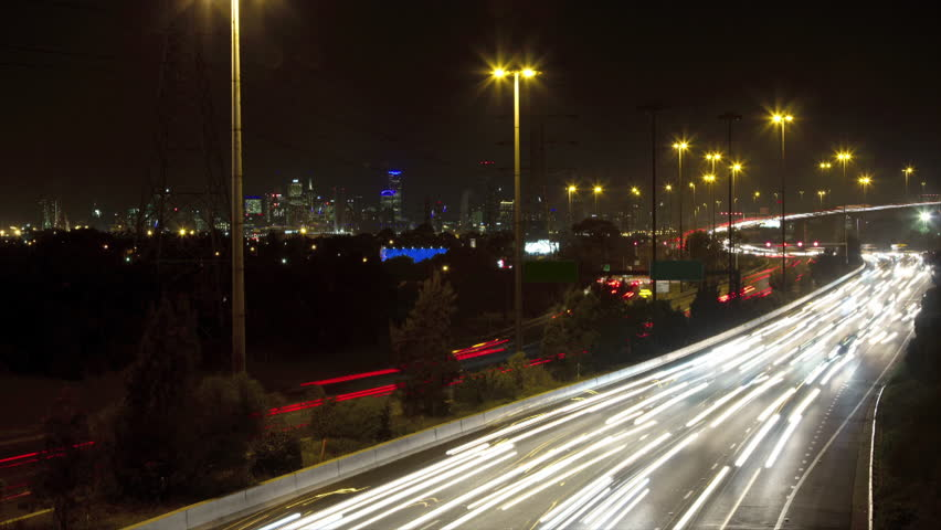 Timelapse at night of busy traffic on freeway with bridge & Melbourne no signs