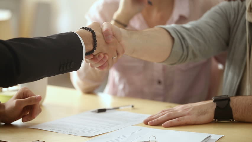 Couple sign mortgage contract, put signature on sale purchase rental agreement, handshaking realtor at meeting with estate agent, satisfied customers buy property, get keys of new home, close up view | Shutterstock Video #31351936