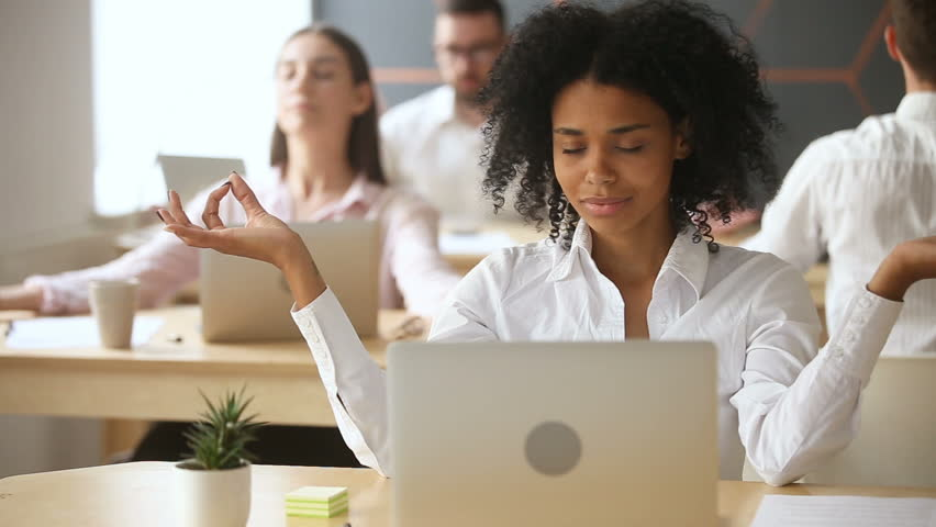 African businesswoman meditating with multiracial colleagues in office, businesspeople doing group yoga exercises indoors at workplace, corporate meditation, keeping mental balance at stressful job