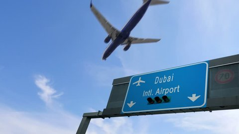 airplane flying over dubai airport signboard