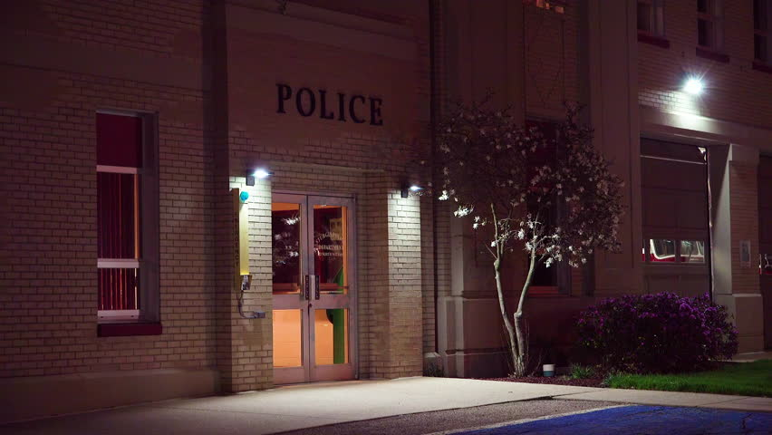 CIRCA 2010s - United States - Exterior establishing shot of a small police station at night.