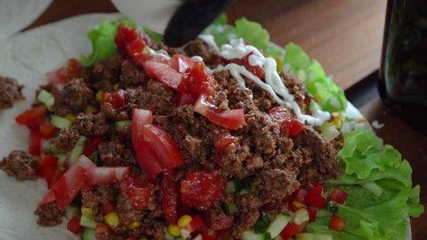 Putting sauce on tacos closeup