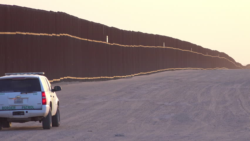 CIRCA 2010s - U.S.-Mexico border - Border patrol vehicle moves near the border wall at the US Mexico border at Imperial sand dunes, California. | Shutterstock HD Video #31373296