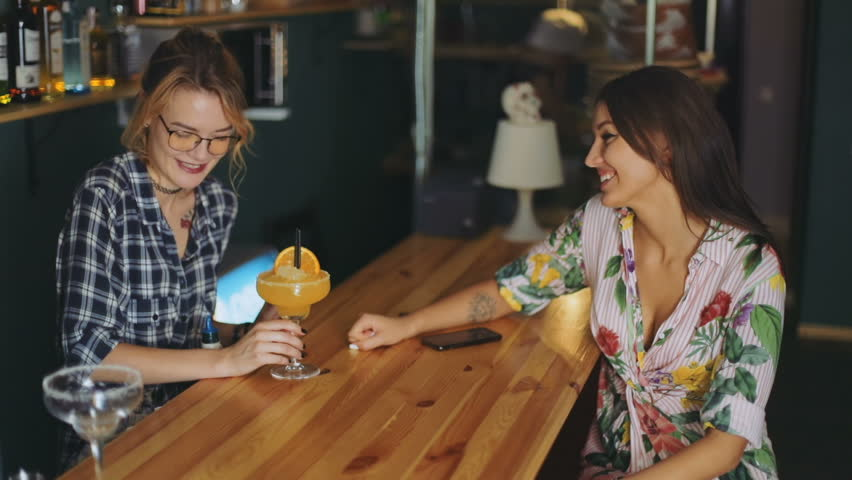 Two happy young female person standing bar counter talking each glass cocktail orange juice waitress barista barmaid amazing attractive woman beautiful dress smiling fun enjoy jouful cheerful speak