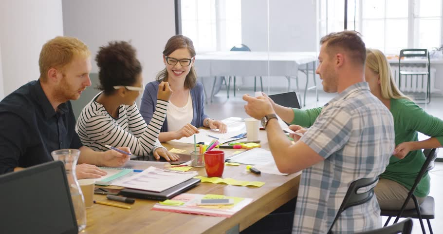 Young diverse coworkers posing at table with documents on top and having lively conversation discussing new ideas. | Shutterstock HD Video #31385626