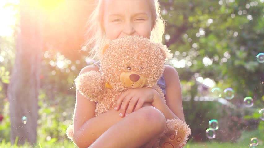 Little cute girl playing with her teddy bear in summer garden. Laughing child sitting on green grass with her toy. Happy childhood concept. Birthday gift. 4K UHD video 3840X2160 slow motion 240 fps
