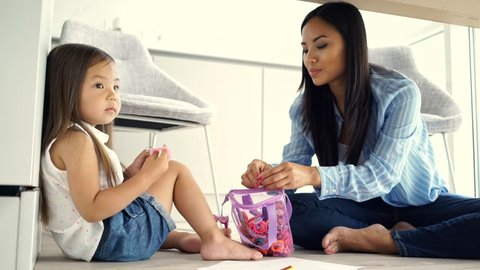 Happy asian woman sitting under table and clings barrette on hair of her displeased daughter