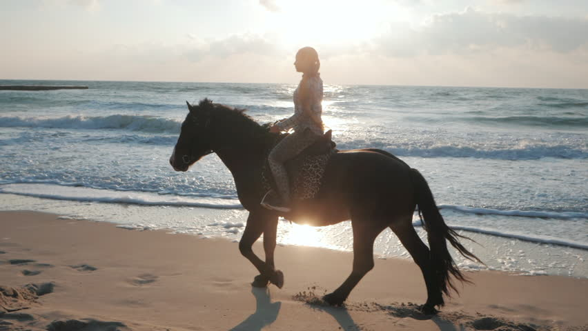 Young beautiful blonde woman with long hair is carefully riding black horse on the seashore. Slow motion. Autumn sunrise or sunset on sea beach. Beautiful scene.