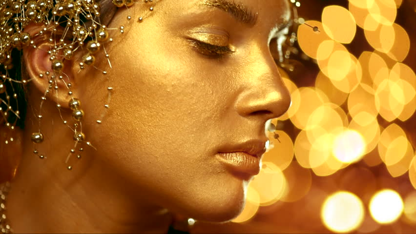 1b2e1f581 Beautiful Model Woman with gold skin makeup. Close up portrait of beauty  girl with golden make up and hair style. Holiday bokeh background.