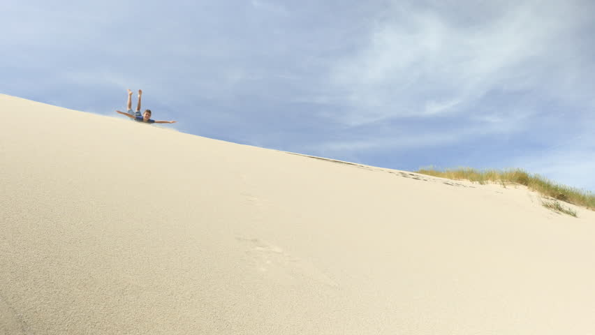 Child Surfing Down Sand Dune Stock Footage Video 100 Royalty Free 31467676 Shutterstock