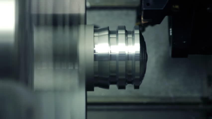 CNC milling machine makes some steel part on a factory
