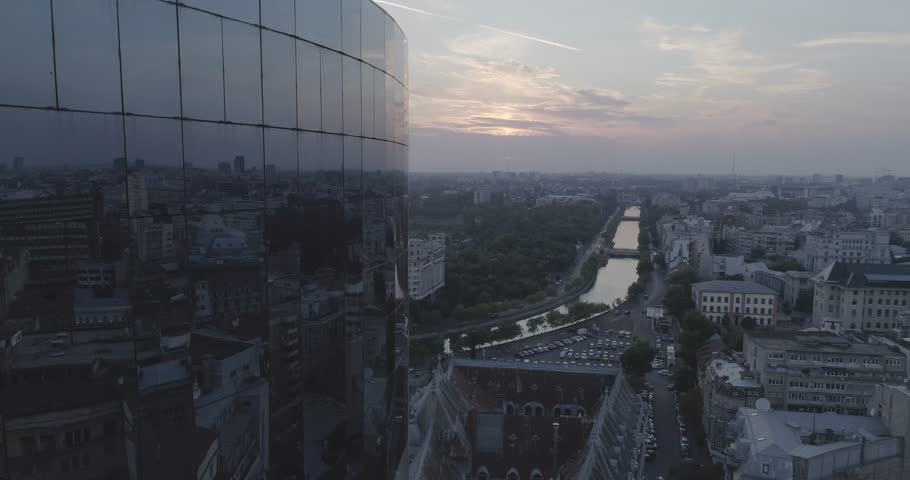 Sunset in Bucharest's old town with river on background and glass skyscraper going up
