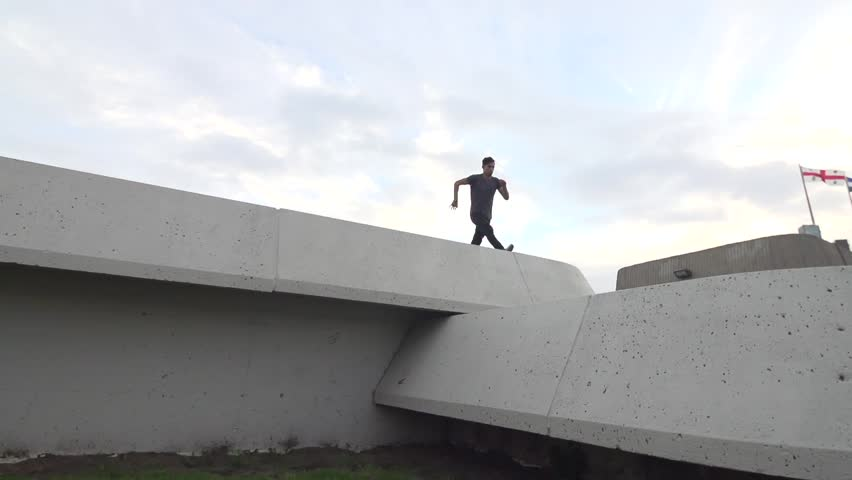 Pro Freerunner - does thred the needle front flip to wall flip on concrete terraced walls. Shot in Slow Motion