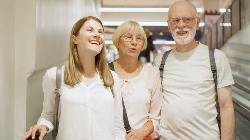 Happy family on escalator in shopping mall. Senior couple and their daughter chatting and laughing on supermarket moving staircase | Shutterstock HD Video #31502386