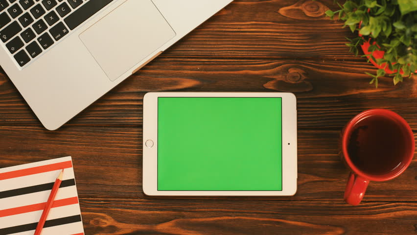 Male fingers scrolling pages on the touchscreen of the white tablet device with green screen on the brown wooden table. Top view. Chroma key. Flat lay | Shutterstock HD Video #31516063