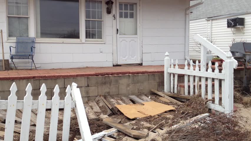 BREEZY POINT, QUEENS, NY-December 2, 2012: Damaged home from waves and storm surge due to Hurricane Sandy. Video pans across demolished front yard and tilts up to reveal home.