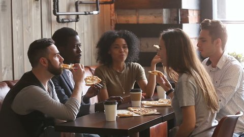 Diverse happy friends eating italian pizza together, five african and caucasian young hungry students enjoying fast food meal sharing lunch during meeting sitting at cozy pizzeria restaurant table