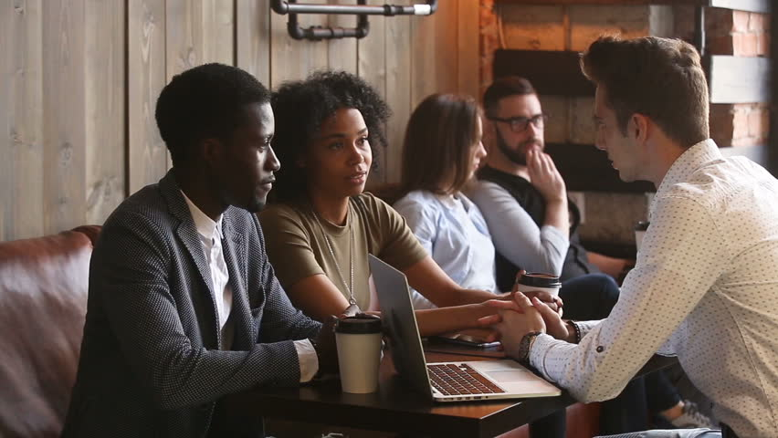 Black couple talking agreeing with white businessman making offer in coffee house, financial advisor or lawyer consulting african family with laptop, diverse people negotiating at meeting in cafe | Shutterstock HD Video #31517626