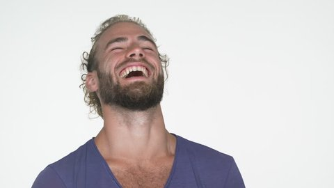 closeup portrait of american handsome guy wearing blue t-shirt looking at camera smiling broadly, laughing out loud with white teeth over white background.