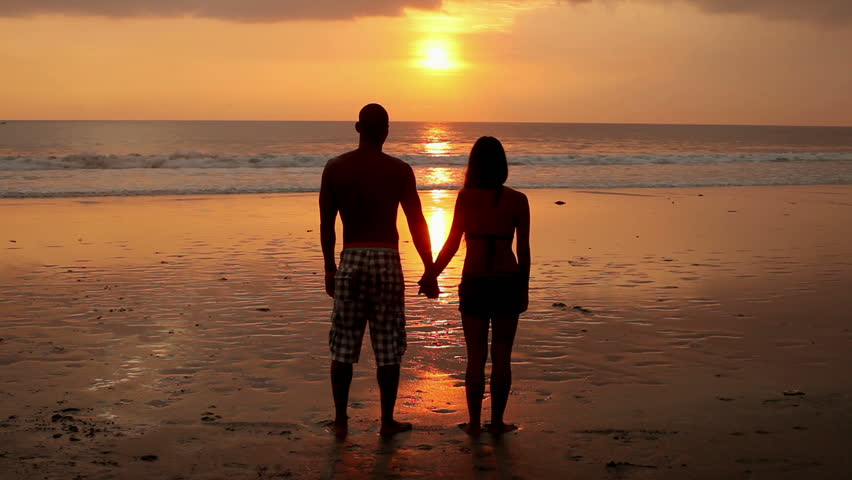 Couple standing hand in hand on beach at sunset in Bali