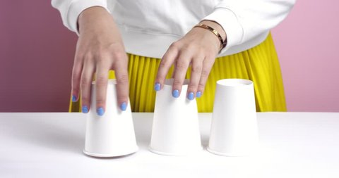 Woman's hands playing with 3 paper cups hiding a ball of foil under one and then switching them around