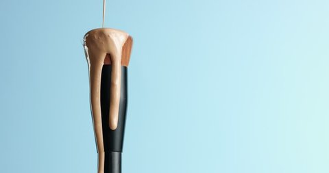Pouring bb cream or foundation on the bristles of a professional make up brush with black handle isolated on blue