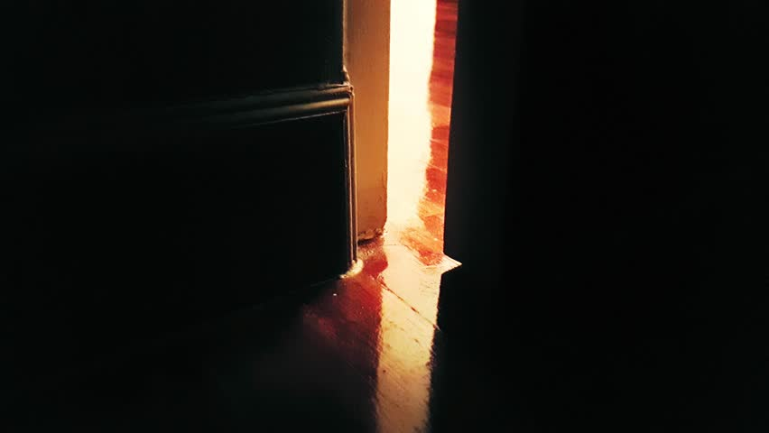 close-up of Door opening in the dark at house with light shining