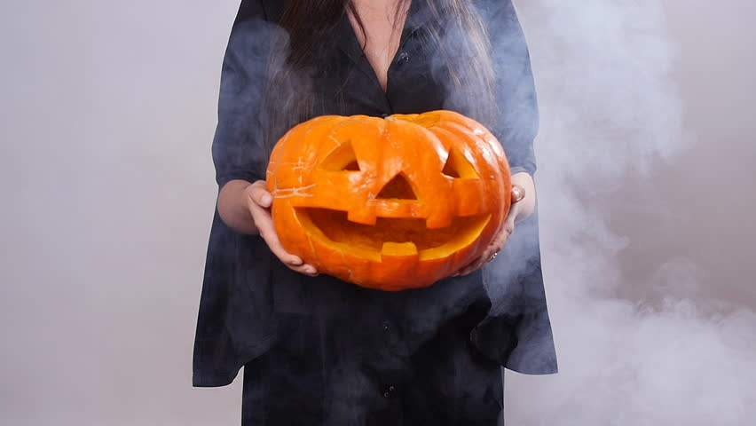 Woman witch is standing with the pumpkin in smoke | Shutterstock HD Video #31542796
