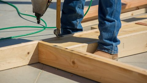 Worker Nails Framing in with Nail Gun and Hammer. a worker uses a nail gun to secure the joints of a wall for a home construction build