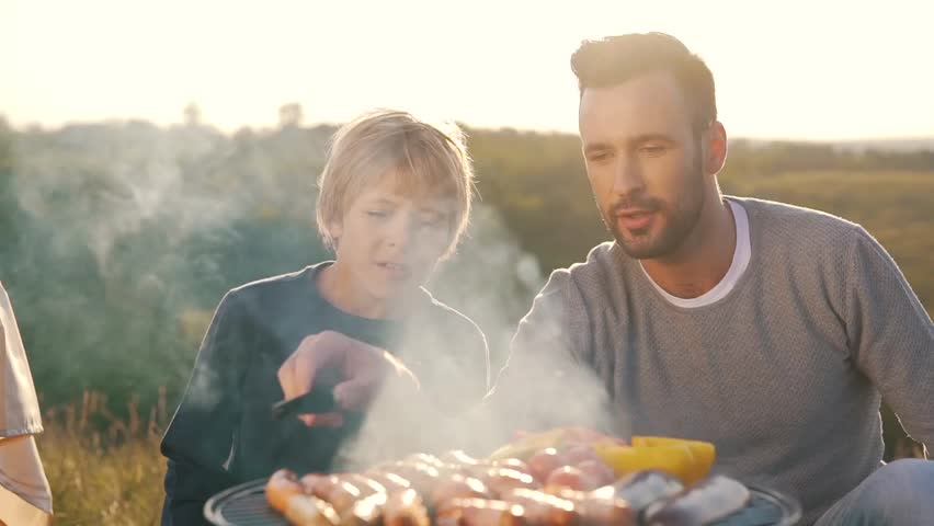 Father and son fry sausages on grill. | Shutterstock HD Video #31551406