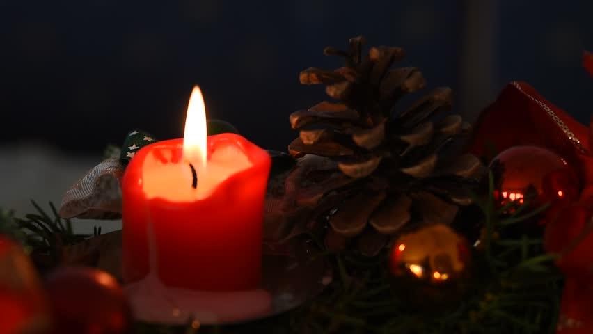 christmas decoration with lighted red candle and cone, romantic mood in advent season