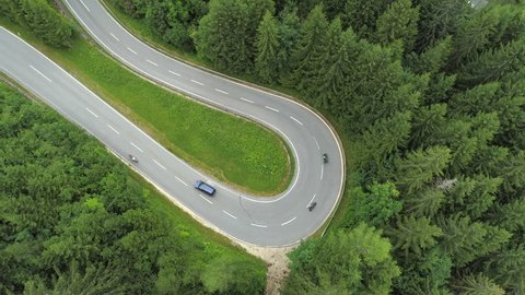 AERIAL: Flying above motorcycles and a car on joyride driving through undulating road on gorgeous lush forested mountain slope in summer. Vehicles traveling on highway speeding through hairpin turn