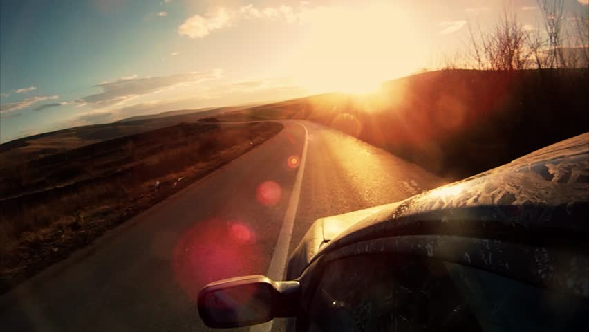 Driving towards the sunset. pov with lens flare.