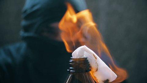 Black bloc anarchist is holding burning molotov cocktail,orange teal look grade