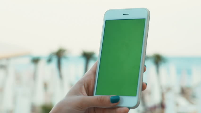 Closeup hand using tapping smart phone green screen chromakey sea summer beach palms unfocused background trendy technology communication people concept resort seaside touching point finger networking