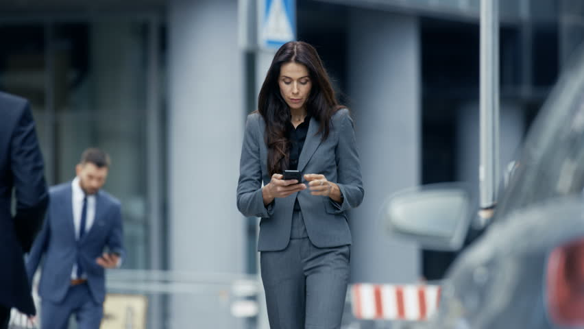 Business Woman in the Tailored Suit Walking on the Busy Big City Street in the Business District, Checks Her Smartphone. Confident Woman on Her Way to do Big Business. Shot on RED EPIC-W 8K Camera. | Shutterstock HD Video #31601170
