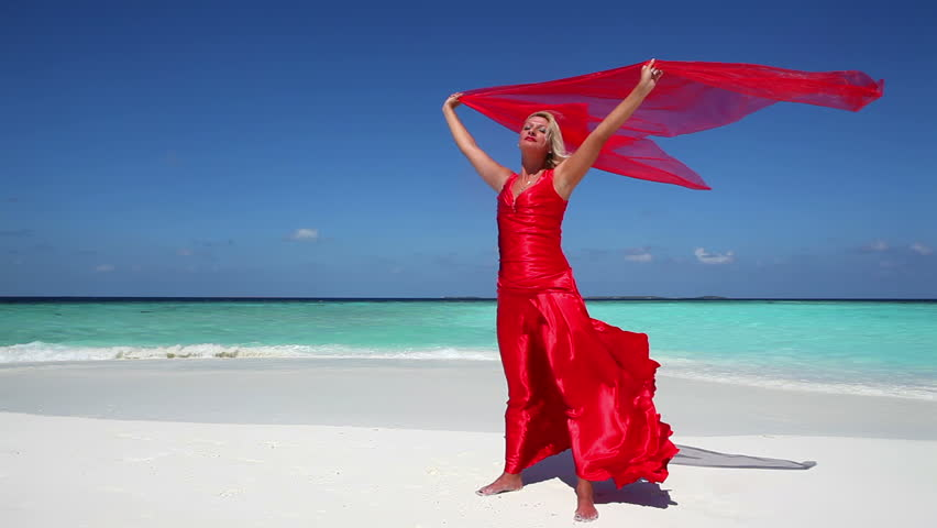 Woman in red dress on the tropical beach  holding a red scarf in the wind