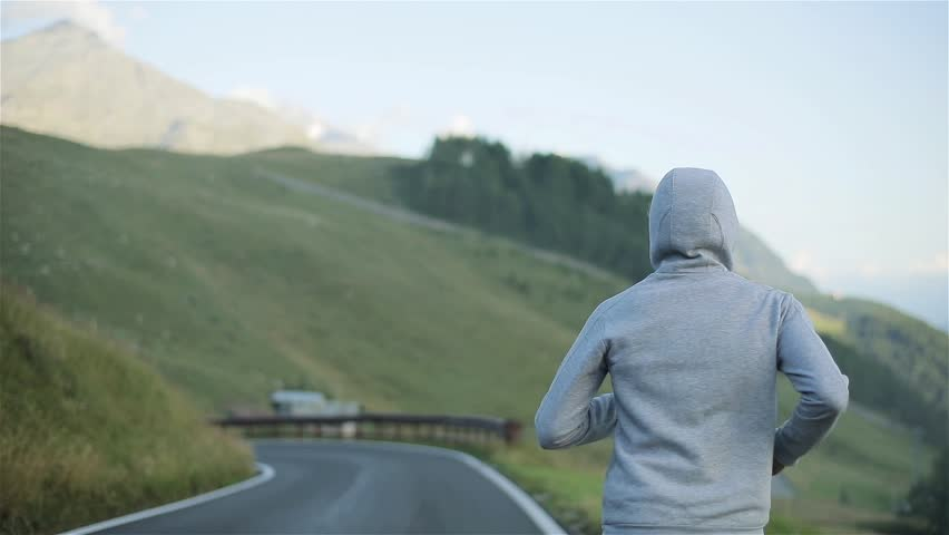 Man jogging back on countryside mountain road in nature close up slow motion. Hooded male figure run followed in morning hill slope background on local asphalt road in grey sportswear and sneakers