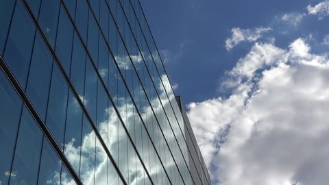 Fluffy white clouds on blue sky mirrored in modern glass building