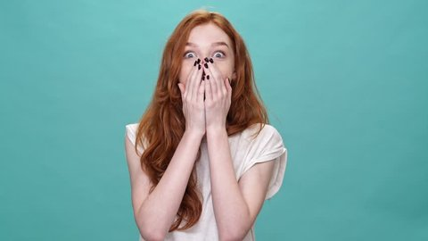 Shocked happy ginger woman in t-shirt covering mouth and looking at the camera over turquoise background