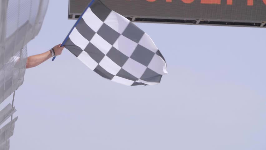 Man holding and waving Checkered race flag in slow motion at finish line on a raceway. Victory, achievement, success and sport concept. | Shutterstock HD Video #31709326