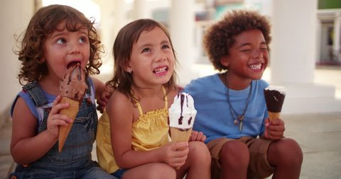 Smiling multi-ethnic children eating ice-cream and having fun together on family summer vacations