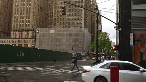 New York-circa 2017: Heavy traffic in the narrow streets of Manhattan, with stunning heights of blocks and bright advertising in the afternoon, on a rainy day, ultra hd4k, real time