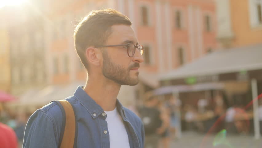 A portrait of a pretty young man in the city. Sun rays in the background. Blurred background | Shutterstock HD Video #31725646